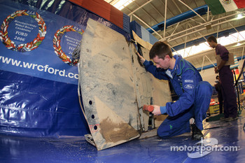 An M-Sport technician works on the undertray of the Jari-Matti Latvala's Ford Focus RS WRC