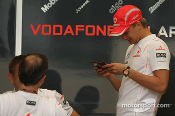 Heikki Kovalainen, McLaren Mercedes on his mobile phone