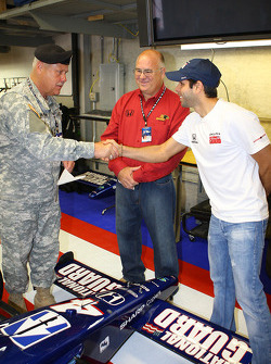 Vitor Meira shakes the hand of a National Guard General after he placed a decal on the No. 4 Panther Racing car