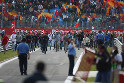 Race fans running on the circuit during the in lap after the race