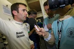 Romain Dumas talks to the media after his crash
