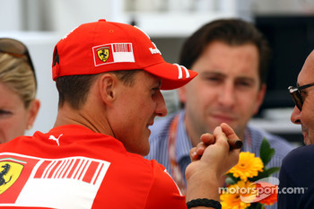 Michael Schumacher, Scuderia Ferrari smokes a cigar in teh Ferrari Hospitality / right: Michel Comte