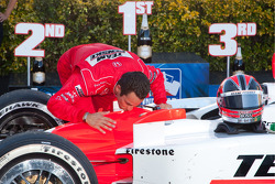 Race winner Helio Castroneves kisses his car to celebrate