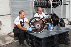 Crew members clean bike wheels