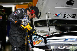 A member of the #17 crew cuts the front fender off after Mastt Kenseth's accident