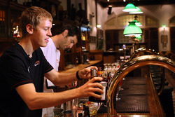 Sebastian Vettel and Mark Webber at the Long Bar of the Raffles Hotel mixing the famous Singapore Sling cocktail