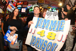 NASCAR Sprint Cup Series champion Jimmie Johnson holds onto a fan's sign as she waits for an autograph at Foley's