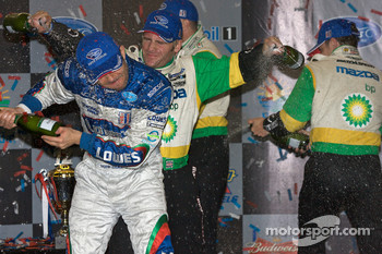 P2 podium: Ben Devlin sprays champagne with two bottles on Luis Diaz