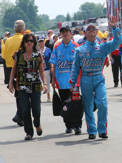 John Andretti waves to the crowd as he walks down Gasoline Alley