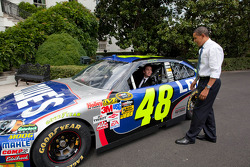 Three-time defending NASCAR Sprint Cup Series champion Jimmie Johnson gets behind the wheel of his No. 48 Lowe's Chevrolet as President Barack Obama looks on at the White House in Washington, D.C.