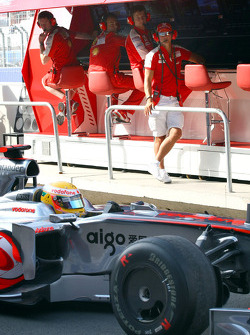 Lewis Hamilton, McLaren Mercedes passes Michael Schumacher, Test Driver, Scuderia Ferrari on the pit wall