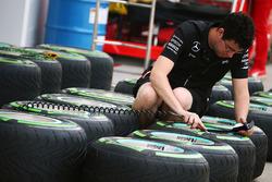 Mercedes AMG F1 Team mechanic works on Pirelli tyres
