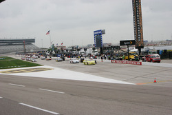 NASCAR Sprint Cup cars speed by NASCAR Nationwide cars parked on pit lane