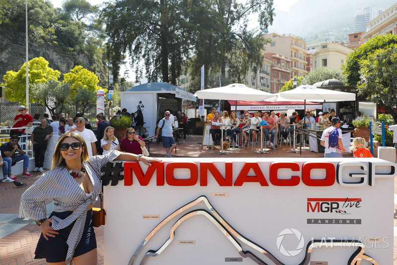 A lady poses next to a Monaco Grand Prix sign