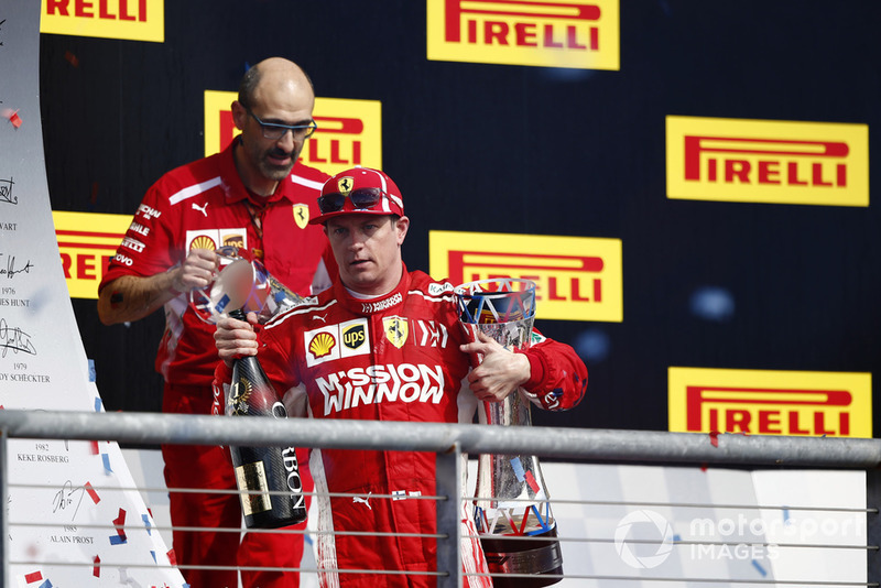 Kimi Raikkonen, Ferrari, with his champagne and trophy on the podium after winning the race