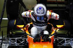 Fernando Alonso, McLaren, lowers himself into the cockpit