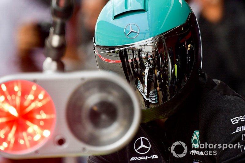Valtteri Bottas, Mercedes AMG F1 W10 parada en boxes se refleja en la visera de un mecánico