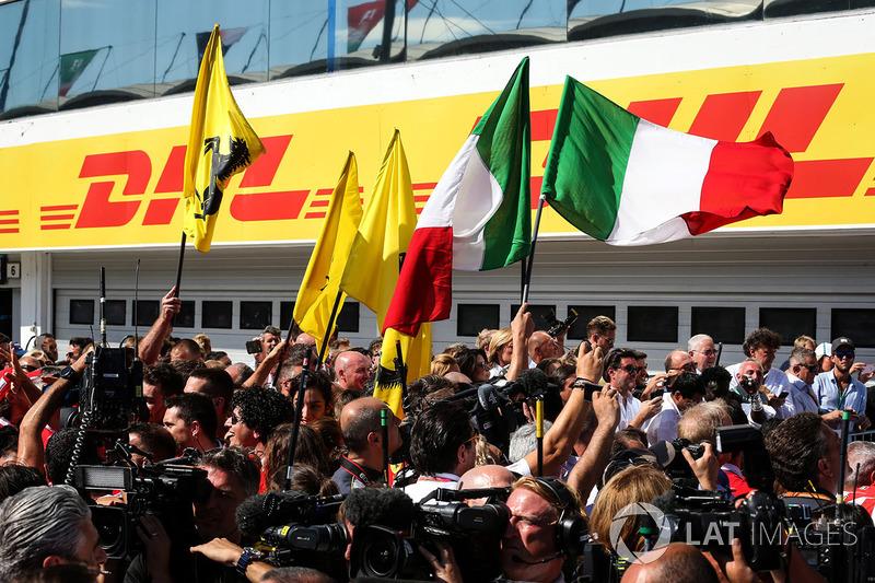 Equipo Ferrari celebra con banderas en parc ferme