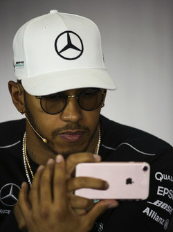 Lewis Hamilton, Mercedes AMG F1, uses his phone, in the Thursday press conference