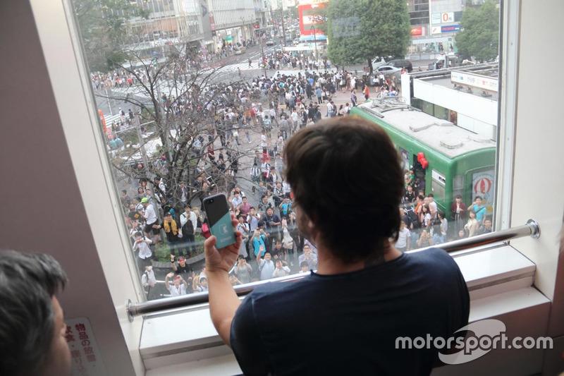 集まったファンをスマートフォンで撮影するアロンソ