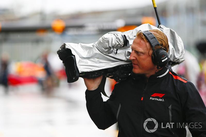 Un caméraman se protège de la pluie