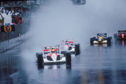 Ayrton Senna leads teammate Gerhard Berger, both McLaren MP4/6 Honda's, Nigel Mansell, Williams FW14 Renault, behind Berger's car in spray, Nelson Piquet, Benetton B191 Ford, and Jean Alesi, Ferrari 643, at the start