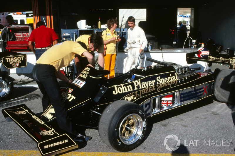 Nigel Mansell, talks to wife Roseanne Mansell, as mechanics work on his Lotus 87 in the pit area