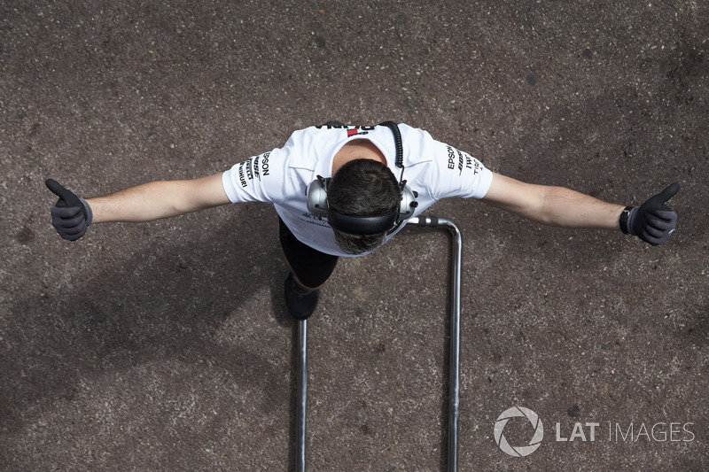 A Williams engineer signals to a driver in the teams garage