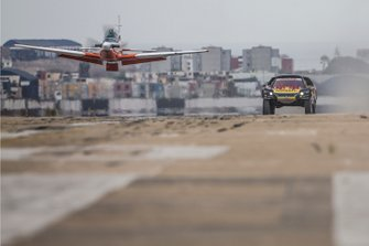 Sebastien Loeb and Daniel Elena of PH Sport make a race with an airplane before the Rally Dakar