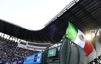 A fan waves a Mexican flag in the grandstand