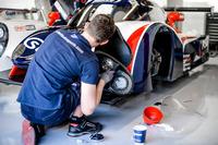Un membro del team United Autosports applica delle decalcomanie