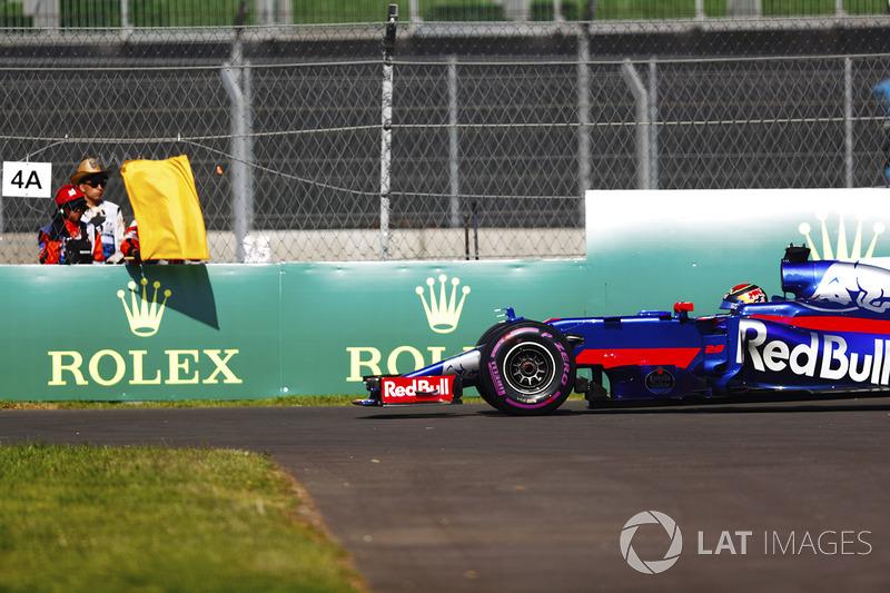 Brendon Hartley, Scuderia Toro Rosso STR12, detenido en pista en los PL1, un mariscal muestra una bandera amarilla