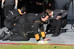 ميكانيكي فريق مكلارين ينظفون أرضية مرآب الفريق