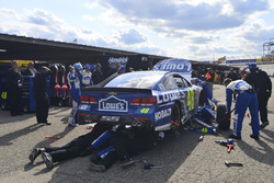 Crew members work on the crashed car of Jimmie Johnson, Hendrick Motorsports Chevrolet