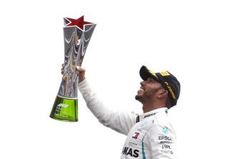Lewis Hamilton, Mercedes AMG F1, celebrates on the podium by raising his winner's trophy