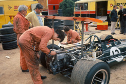 BRM mechanics work on Jackie Oliver's P133 in the paddock as Tony Rudd looks on
