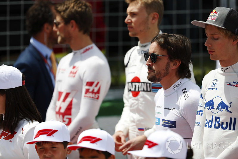Fernando Alonso, McLaren, stands to attention for the national anthem, next to Brendon Hartley, Toro