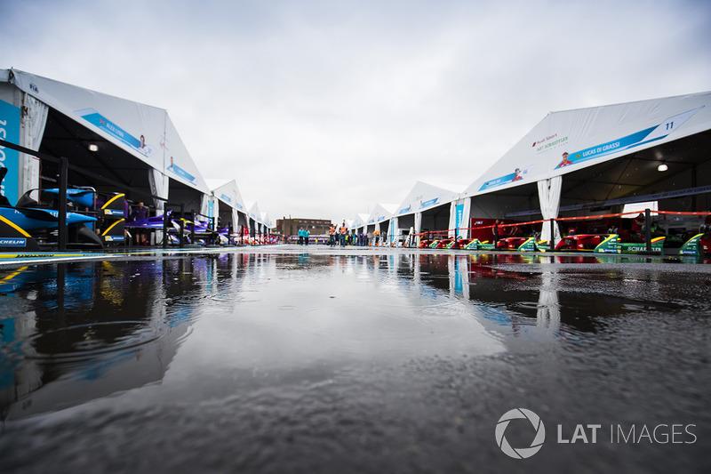 La lluvia cae en un charco en el paddock