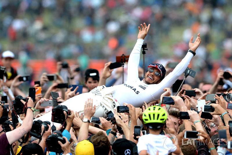 Il vincitore della gara Lewis Hamilton, Mercedes AMG F1 festeggia con i fan nel parco chiuso facendo surf sulla folla