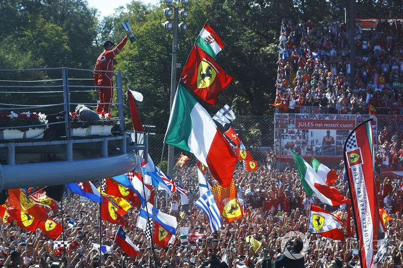 Sebastian Vettel menunjukkan trofi peringkat ketiga ke Tifosi