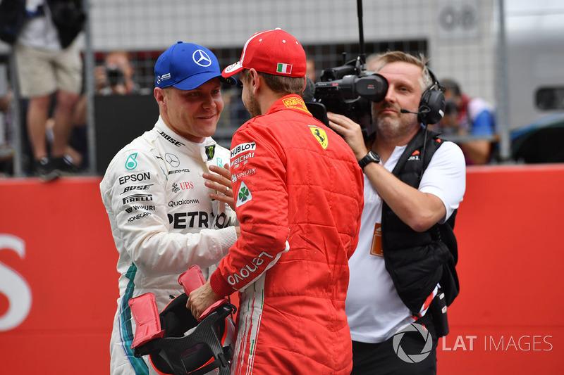 Il poleman Valtteri Bottas, Mercedes-AMG F1 e il terzo qualificato Sebastian Vettel, Ferrari, festeggiano nel parco chiuso