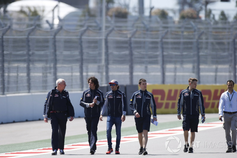 Carlos Sainz Jr., Toro Rosso, walks with team members, including former Manor boss John Booth