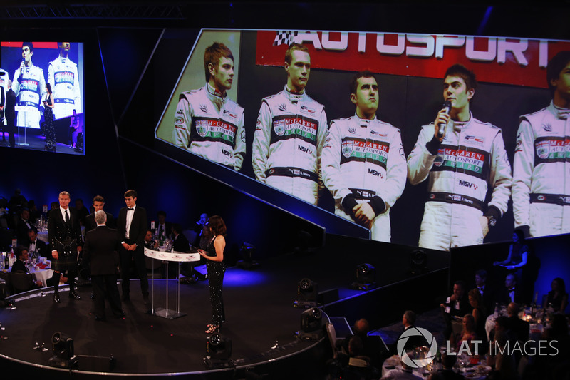 Derek Warwick receives an award from george Russell and Lando Norris. On the big screen is an image of previous MABA finalists, including Lewis Williamson and Scott Malvern