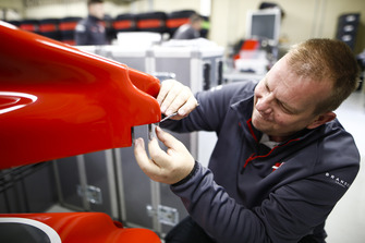 A Haas team member works on a nose cone