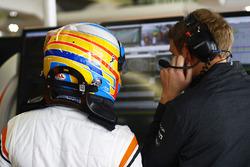 Fernando Alonso, McLaren, talks with his engineer in the garage