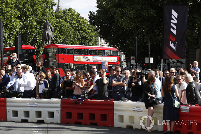 A London Routemaster, F1 advertising behind a group of fans