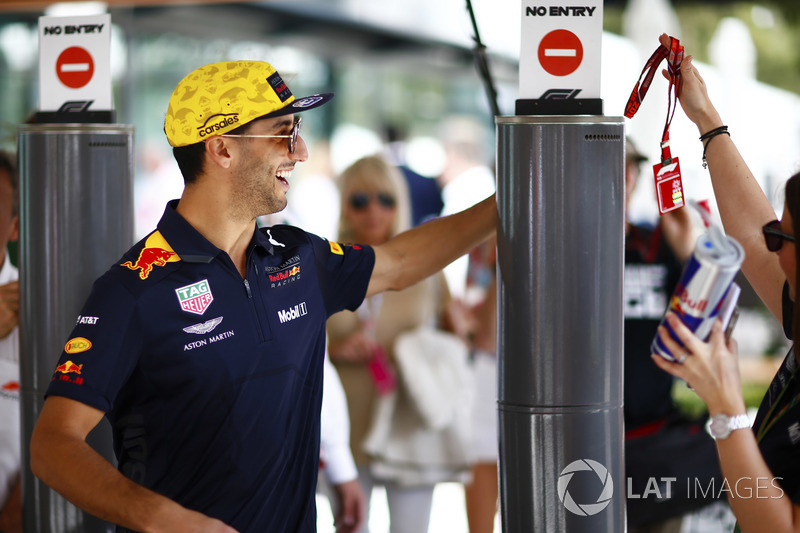 Daniel Ricciardo, Red Bull Racing, is handed a pass as he passes through the paddock gates