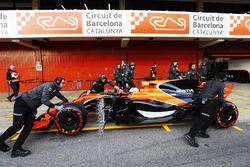 McLaren team members push the McLaren MCL32 of Fernando Alonso, McLaren, in the pit lane