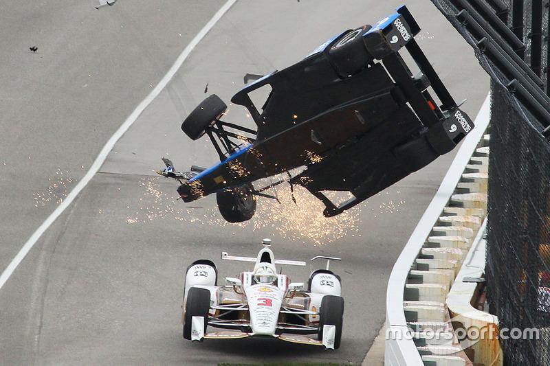 L'accident de Scott Dixon, Chip Ganassi Racing Honda, en dessous de quoi passe Helio Castroneves, Team Penske Chevrolet