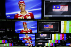 Sebastian Vettel, Ferrari, is pictured on television screens in the media centre